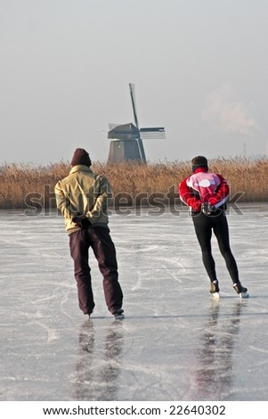 Typically dutch: ice skating on a frozen lake with view on a windmill on a cold winterday - stock photo