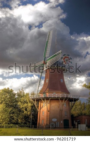 Typically historical windmill in East Friesland in the summer with storm clouds - stock photo