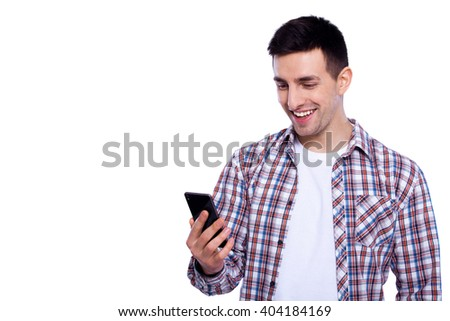 Typing a message. Cheerful young man reading message on the mobile phone and smiling while standing isolated on white background