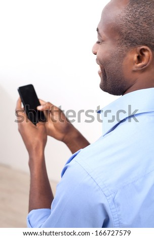 Typing a message. Rear view of cheerful black man typing something on the mobile phone and smiling while standing isolated on grey - stock photo