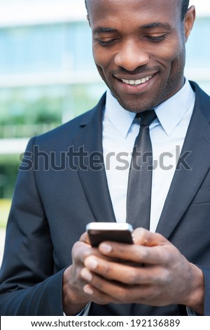 Typing business message. Cheerful young African man in formal wear holding mobile phone and smiling while standing outdoors - stock photo