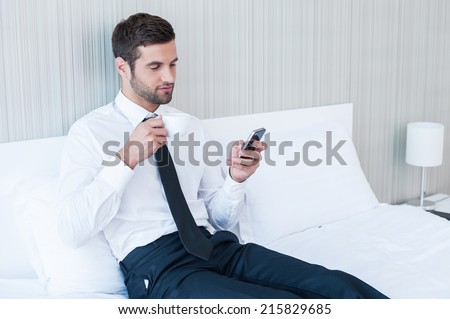 Typing business message. Confident young man in shirt and tie drinking coffee and holding mobile phone while lying in bed at the hotel room  - stock photo