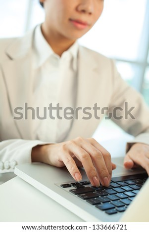 Typing female hands on the foreground - stock photo