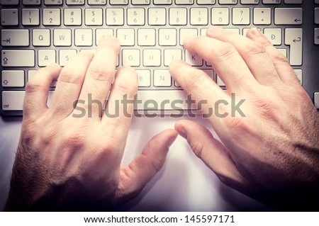 Typing hands on the keyboard from above