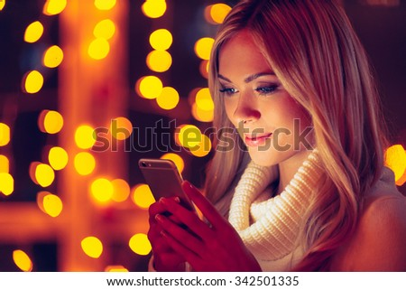 Typing lovely message to him. Beautiful young smiling woman in white sweater holding smart phone and looking at it with defocused Christmas lights in the background - stock photo
