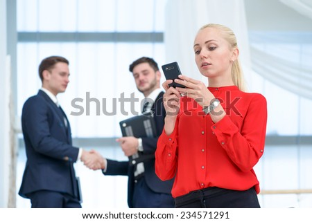 Typing message. Confident businesswoman standing on a ladder and gaininga message on your cell phone while her colleague businessmen shaking hands in the background - stock photo