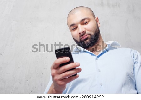 Typing message. Handsome young man in shirt using mobile phone while leaning on grey wall. - stock photo