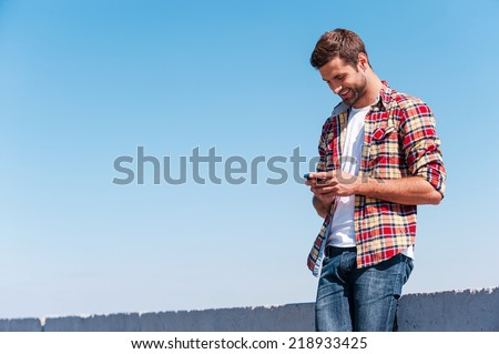 Typing message to friend. Cheerful young man holding mobile phone and looking at it while standing outdoors with blue sky as background  - stock photo