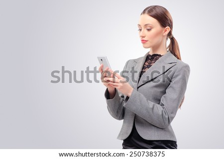 Typing message to friend. Confident young woman holding mobile phone and looking at it while standing against studio background - stock photo
