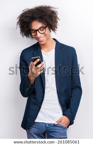 Typing message to friend. Handsome young African man holding mobile phone and smiling while standing against grey background  - stock photo