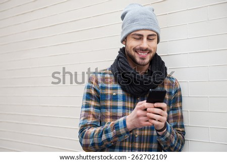 Typing message to friend. Handsome young man holding mobile phone and looking at it while leaning brick wall  - stock photo