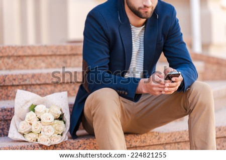 Typing message to girlfriend. Close-up of handsome young man in smart jacket looking at the mobile phone and while sitting on the staircase with bouquet of roses laying near him - stock photo