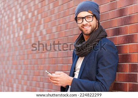 Typing text message. Side view of handsome young man in smart casual wear holding mobile phone while leaning at the brick wall - stock photo