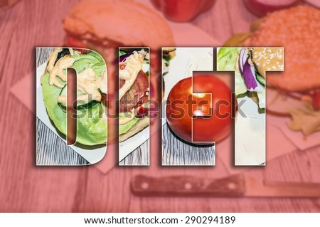 Typography poster. Blurred background with vegetables and burgers on the wooden desk with inscription DIET - stock photo
