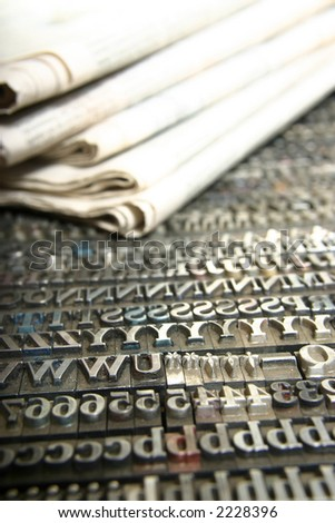 Typography workshop .Old Metallic Letters for Printing with daily newspaper - stock photo