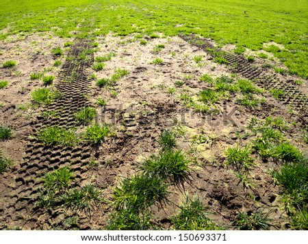 tyre tracks on a muddy sports field - stock photo