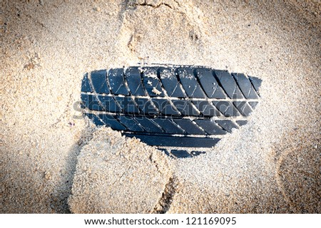 Tyre under sand on the beach - stock photo