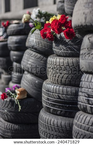Tyres cars stacked in columns. The top is a memorial bread and flowers. Location Kiev, Maidan Nezalezhnosti. Close-up. - stock photo