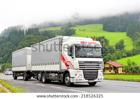 TYROL, AUSTRIA - JULY 29, 2014: White cargo truck DAF XF at the high mountain road. - stock photo