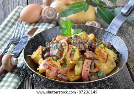Tyrolean fried potatoes with meat, bacon and mushrooms (Tyrolean Groestl) - stock photo