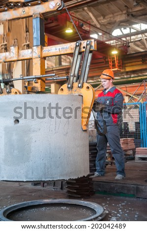 TYUMEN, RUSSIA - AUG 13, 2013: Circle pit making department at construction material factory ZHBI-5 (Concrete Goods Plant No. 5). Worker moves prepared unit to warehouse