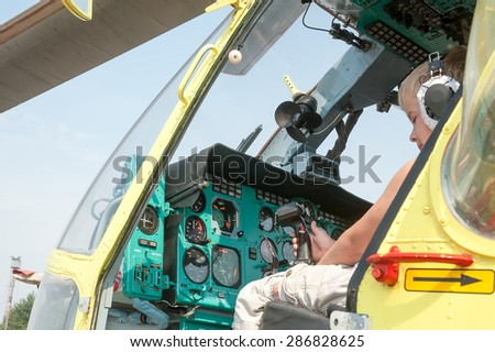 """Tyumen, Russia - August 11, 2012: Air show """"On a visit at UTair"""" in heliport Plehanovo. Little boy sitting in cabin of MI-8 helicopter - stock photo"""