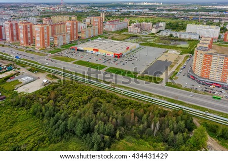 Tyumen, Russia - August 7, 2015: Okey shopping mall of household goods with a lot of parking space, East-2 residential district. Aerial view - stock photo