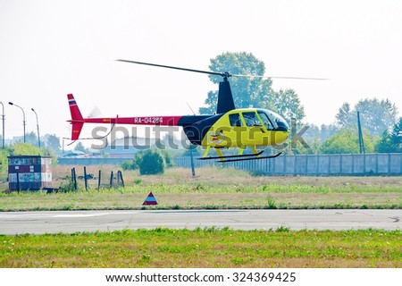 Tyumen, Russia - August 11, 2012: On a visit at UTair airshow in heliport Plehanovo. Pilot of Robinson R44 Raven shows flying opportunities - stock photo