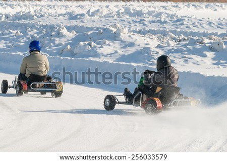 "Tyumen, Russia - February 22, 2015: Ice autodrome ""Ice cult"" on Alebashevo lake. Man is driving Go-kart with speed on karting track - stock photo"