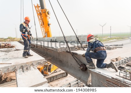 Tyumen, Russia - July 31, 2013: JSC Mostostroy-11. Bridge construction for outcome of the Tobolsk path and Bypass road round Tyumen. Workers establish bridge span - stock photo