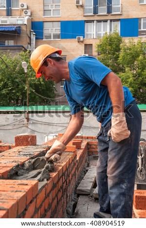 Tyumen, Russia - July 31, 2013: JSC Mostostroy-11. Construction of 18 floor brick residental house at the intersection of streets of Nemtsov and Tsiolkovsky. Bricklayer on house constructionwork - stock photo