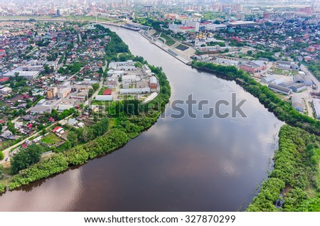 Tyumen, Russia - June 3, 2015: Chemical and pharmacological factory on Tura river. Tyumen state architectural and construction university, quay and Holy Trinity Monastery - stock photo