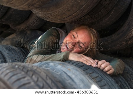 Tyumen, Russia - June 11, 2016: Race of Heroes project on the ground of the highest military and engineering school. Athlete moves between old tires. Born again stage - stock photo