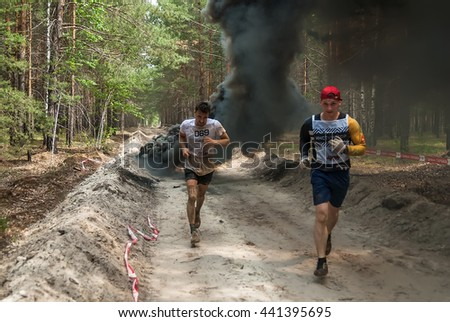 Tyumen, Russia - June 11, 2016: Race of Heroes project on the ground of the highest military and engineering school. Sportsmen run between stages - stock photo