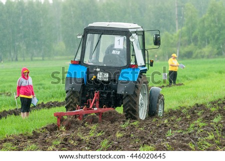 Tyumen, Russia - June 24, 2016: The 5th open championship of Russia on a plowed land. Young operator plows the site on Belarus tractor in rainy weather. Judges check quality of work - stock photo