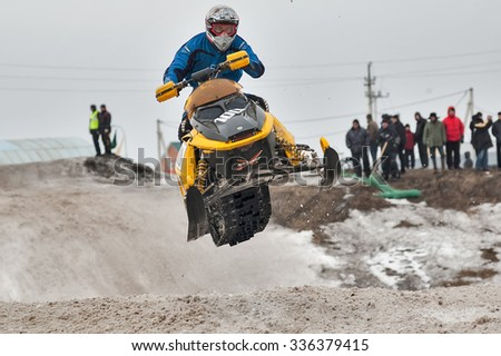 Tyumen, Russia - March 08. 2008: IV stage of personal-team Championship of Ural Federal district in over-snow cross-country. High jump of sportsman on snowmobile - stock photo