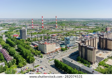 Tyumen, Russia - May 25, 2015: Aerial view onto office buildings, residential district on Harkovskaya street and combined heat and power factory - stock photo