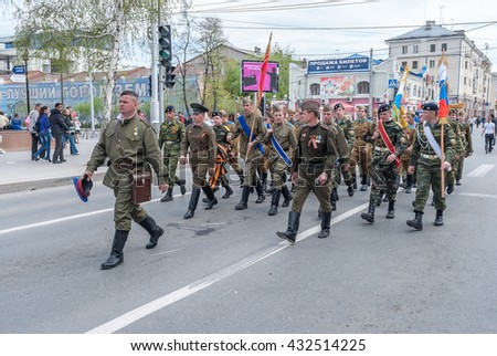 Tyumen, Russia - May 9. 2010: Parade of Victory Day in Tyumen. Men in the uniform of times of the Great Patriotic War and modern marching - stock photo