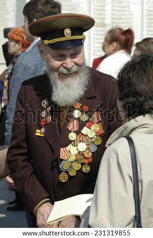 Tyumen, Russia - May 8. 2006: Wreath-laying ceremony to Eternal flame. Senior veteran of World War II on Memory square - stock photo