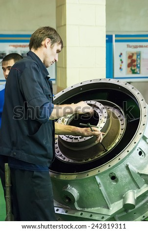 Tyumen, Russia - November 14, 2007: JSC Tyumenskie Motorostroiteli (Plant on production and repair of aviation engines). Mechanic assembles part for aviation engine - stock photo