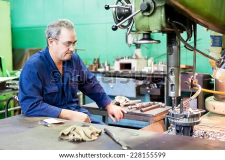 Tyumen, Russia - September 7, 2010: JSC Tyumenskie Motorostroiteli (Plant on production and repair of aviation engines). Senior milling machine operator works at machine - stock photo