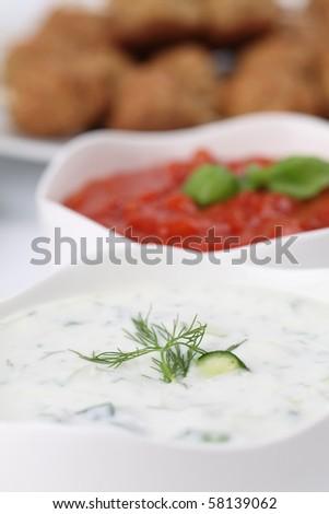 Tzatziki - Greek yogurt sauce with cucumbers, dill and garlic, known as tarator or snezhanka in Bulgaria or zaziki in Turkey and tomato sauce. Shallow DOF - stock photo