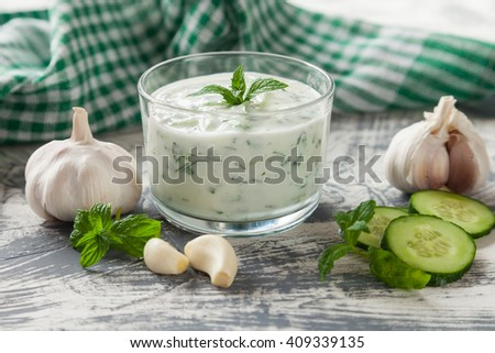 Tzatziki sauce in bowl, with ingredients - cucumber, mint, dill, lemon,  selective focus