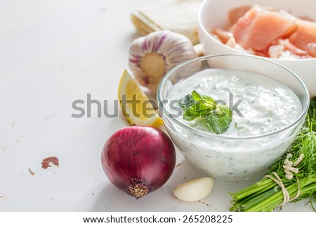 Tzatziki sauce in glass bowl, with ingredients - cut cucumber, mint, dill, lemon, garlic and meat for souvlaki, white wood background - stock photo