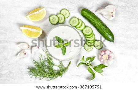 Tzatziki sauce ingredients. Yoghurt, herbs and vegetables. Food background - stock photo