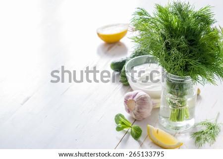 Tzatziki sauce ingredients - yogurt, cucumber, lemon, mint, dill on white wood background - stock photo