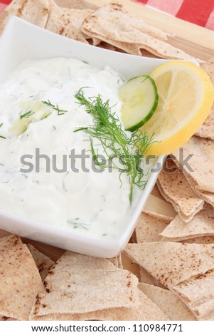 Tzatziki sauce made with yogurt, cucumbers, dill and lemon in a bowl with pita chips on the side