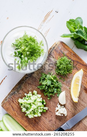 Tzatziki sauce preparation - yogurt in glass bowl, cut cucumber, mint, dill, knife, white wood background, top view - stock photo