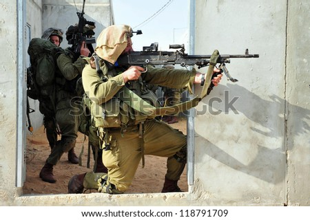 TZEELIM - MARCH 31: Israeli soldier shoots during Urban Warfare Exercise on March 31 2011 in Tzeelim, Israel. The complexity of the terrain and civilians makes it very difficult to identify the enemy - stock photo