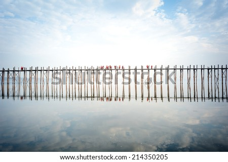 U bein bridge in Myanmar with many Buddhist monks crossing it at early morning sunrise - stock photo